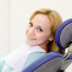 Patient seated at Dentist chair smiling at camera