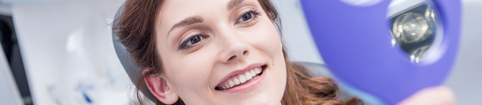 Cropped image of a female patient smiling and looking at her teeth in a hand mirror