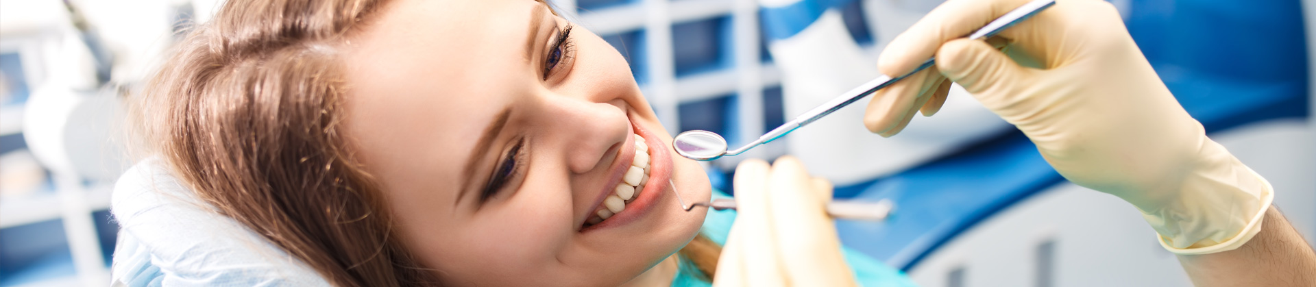 Smiling patient getting treatment at Dental clinic