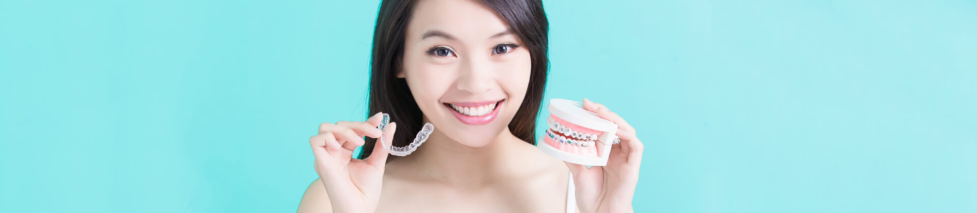 Closeup of woman holding invisalign bracers and a denture