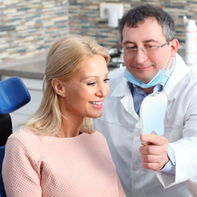Dentist holding a mirror in front of patient