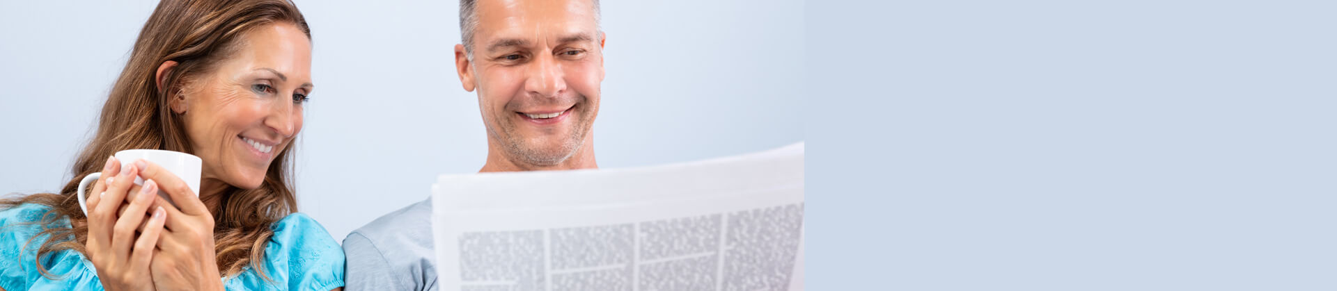 Portrait of happy mature couple reading newspaper at home
