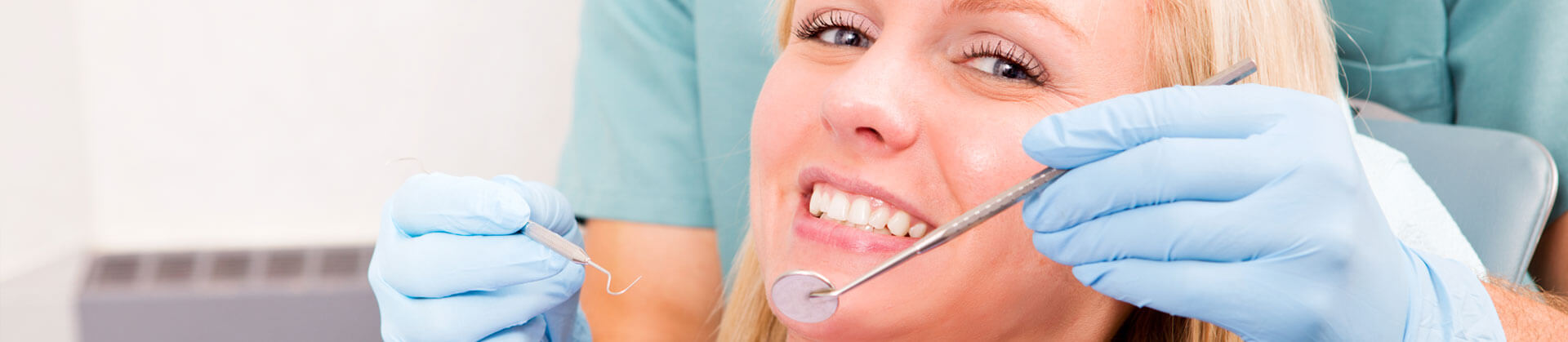 Cropped view of smiling woman getting dental treatment