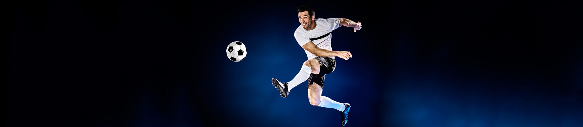 Man playing soccer isolated in dark background